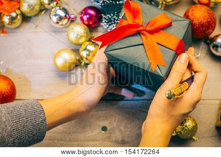 man hand holding gift box with a pen in his right hand.