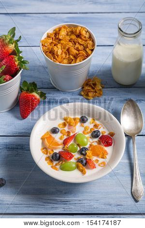 Corn flakes with fruit and milk on old wooden table