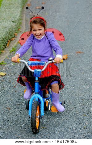 Happy little girl age 05 dressed with lady bug costume ride a bike outdoor. photo with copyspace