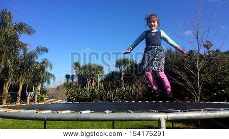 Happy Little Girl Bouncing On Trampoline