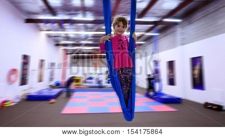 Little Child Learn Circus Skills On Aerial Strap