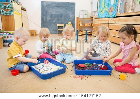 Children improving hands motor skills with rice and beans