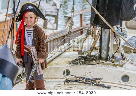 young happy child dressed like a pirate sailing an old wooden ship