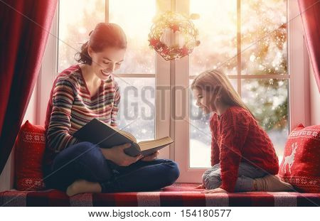 Merry Christmas and happy holidays! Happy loving family sitting by the window. Room decorated on Christmas. Pretty young mother reading a book to her daughter.