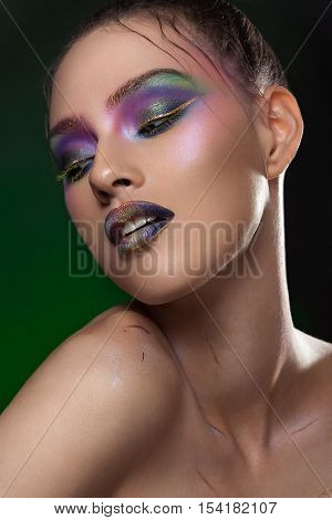 Model girl with vivid make up on dark green background. Conceptual beauty make up