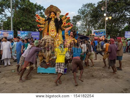 KOLKATA, INDIA - OCTOBER 11, 2016: Puja workers push Durga idol to the Ganges river for immersion at Babughat Kolkata, West Bengal, India. The five day Durga puja concludes with idol immersion.