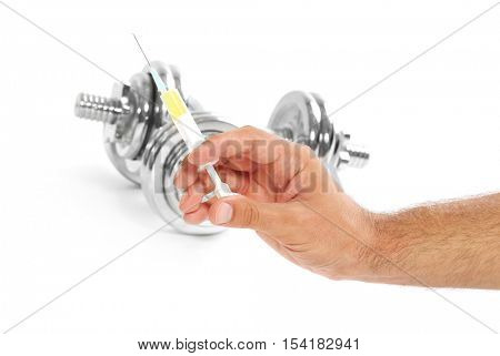 Male hand holding syringe and dumbbells on background