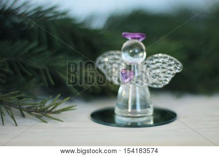 Glass angel decoration and Christmas tree branch as background