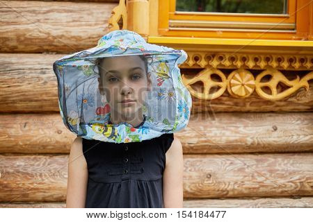 Teenage girl in hat with bee veil stands against wooden house.