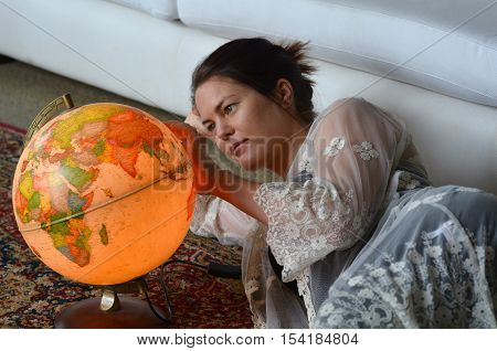 Young woman search for a travel destination on a vintage globe. Travel concept