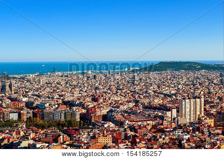 an aerial view of Barcelona, Spain, seen from the Turo de la Rovira hill, with the Montjuic Hill highlighting to the right, and the Mediterranean sea at the background