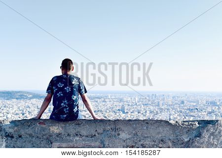 a young caucasian man, seen from behind, sitting at the top of a hill observing the city below him