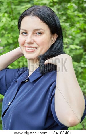 Portrait of dark-haired smiling woman in green summer park.