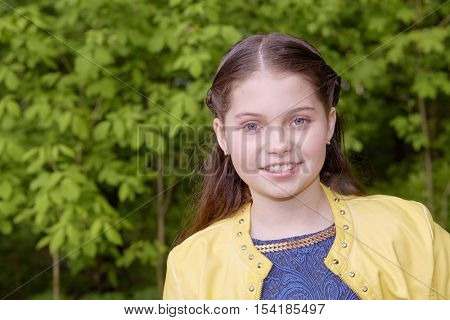 Humeral portrait of smiling girl in yellow jacket in green park.