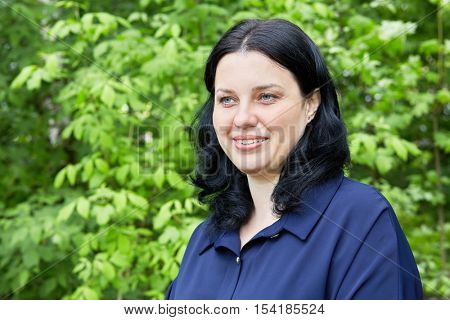 Humeral portrait of dark-haired smiling woman in green summer park.