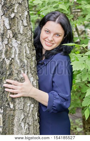 Portrait of smiling dark-haired woman peeking out from behind the tree in green summer park.