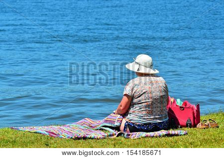An old woman daydreaming on a lake bank. Retirement concept with copy space