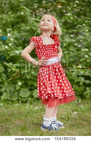 Little girl in red polka-dotted dress stands with  her hands akimbo and looking upward at grassy lawn.