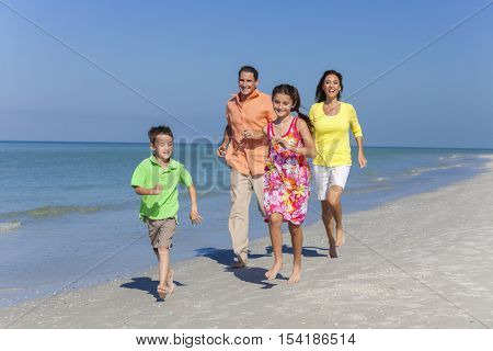 A happy family of mother, father and two children, son and daughter, running and having fun in the sand of a sunny beach