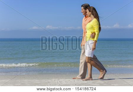Man and woman romantic couple in colorful clothes walking on a deserted tropical beach with bright clear blue sky