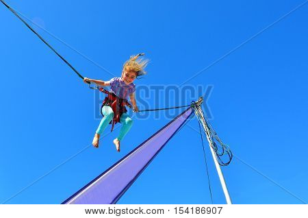 Little girl (age 5-6) on Bungee trampoline. Concept risk with copy space