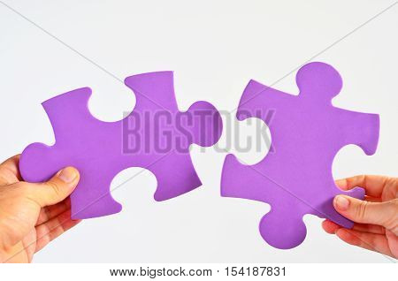 Man and woman hands holds two different puzzle pieces separated on a white background.Relationship concept poster