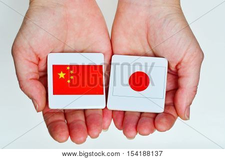 Two Hands Holds The National Flags Of The Republic People Of China (l) And Japan (r)