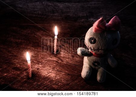 Vintage evil spooky doll with light of candle in darkness on wooden table halloween concept.