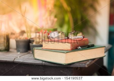 Glasses with books and pen on wood table in morning time. weekend lifestyle concept. focus on red vintage book spine