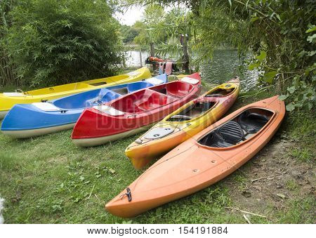 Several single and double kayaks on the riverside in cloudy day