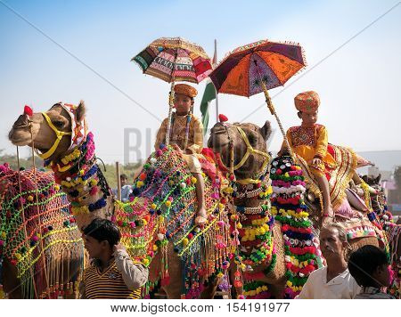 PUSHKAR INDIA - NOVEMBER 222012: Many adults and children attends at traditional camel decoration competition at camel mela in Pushkar. People from all over Rajasthan flock to annual fair.