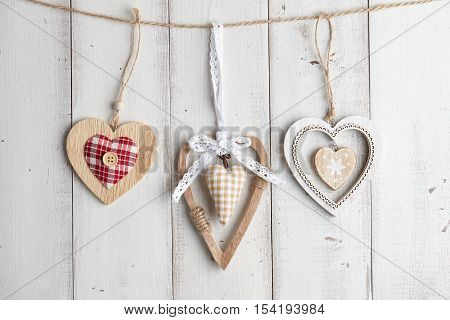 Wooden valentine hearts hanging over white fence