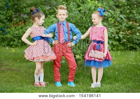 Boy in red trousers and blue shirt stands with two girls at grassy lawn.