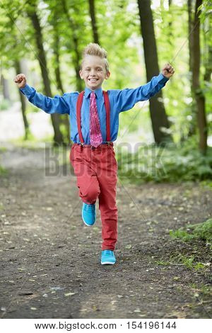 Happy boy in red trousers with braces and blue shirt runs along path in summer park.