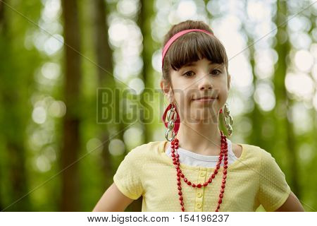 Portrait of girl with red necklace, earrings and red headband standing in summer park.