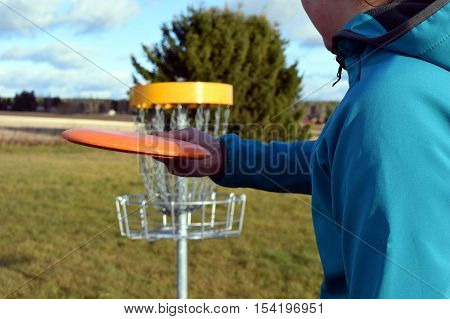 Teenager aiming disc on disc golf course.