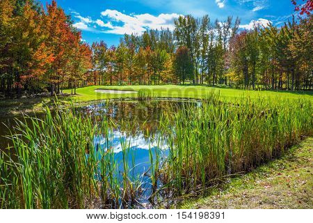 Concept of recreational tourism. Shining day in French Canada.  Autumn foliage reflected in clear water of the pond. Charming pond in the picturesque park