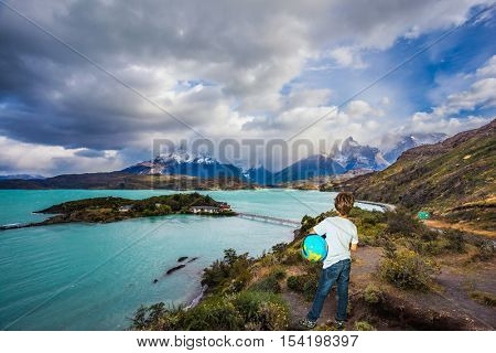 Boy with a globe under his arm on lake Pehoe. Chile, Patagonia, Torres del Paine National Park - Biosphere Reserve