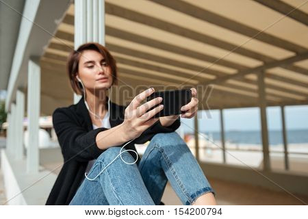 Beautiful young woman sitting and listening to music from cell phone in verandah on the beach