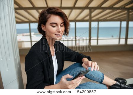 Happy pretty young woman using cell phone in verandah on the beach