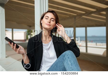 Smiling young woman listening to music from mobile phone in verandah on seashore