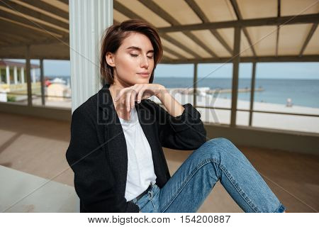 Beautiful young woman sitting with eyes closed and relaxing in verandah near the sea