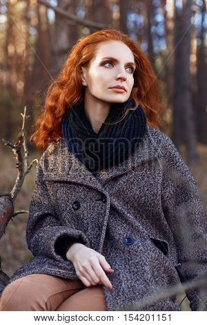 Beautiful red-haired woman. Redhead girl in autumn clothes outdoors. Redhead woman outdoor in autumn park weared scarf and coat. Autumn fashion look