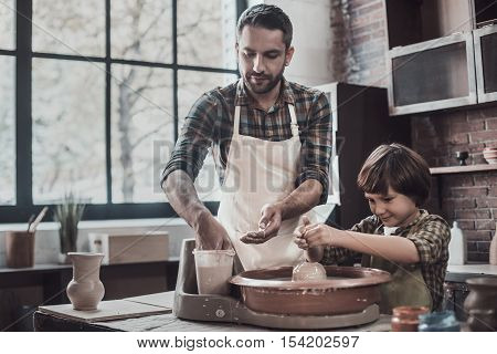 Pottery class. Confident young man and little boy making ceramic pot on the pottery class