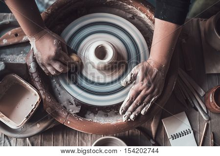 Potter at work. Top view of potter making ceramic pot on the pottery wheel