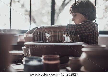 Child on pottery class. Confident little boy making ceramic pot on the pottery class