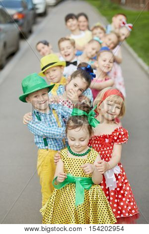 Fifteen children stand one by one bending to defferent sides at sidewalk, focus on first girl.
