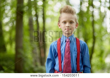 Portrait of boy wearing red trousers with braces, blue shirt, red tie in summer park.