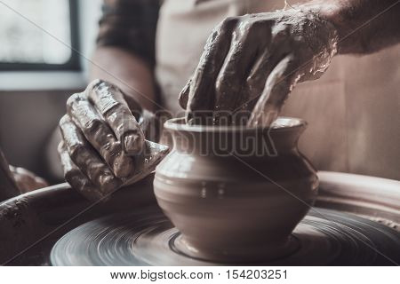 Close-up on creative work. Close-up of man making ceramic pot on the pottery wheel