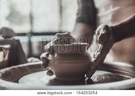 Potter at work. Close-up of man making ceramic pot on the pottery wheel